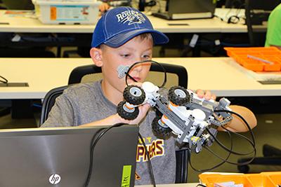 Student examining Lego robot