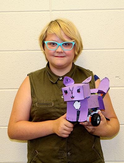 Student holding Lego robot